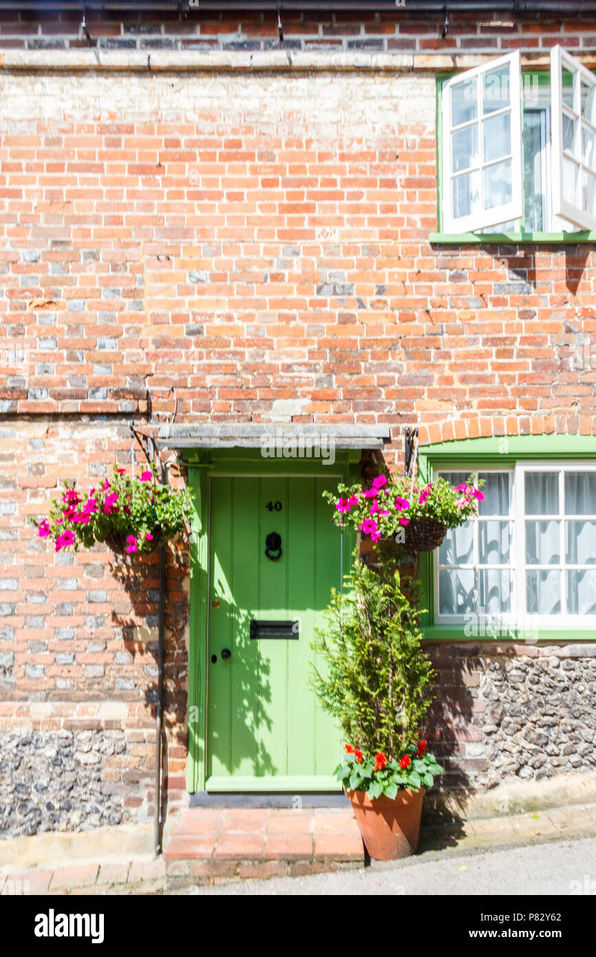 Country cottage green door with hanging baskets and open window, West Wycombe, Buckinghamshire, England,UK - Stock Image