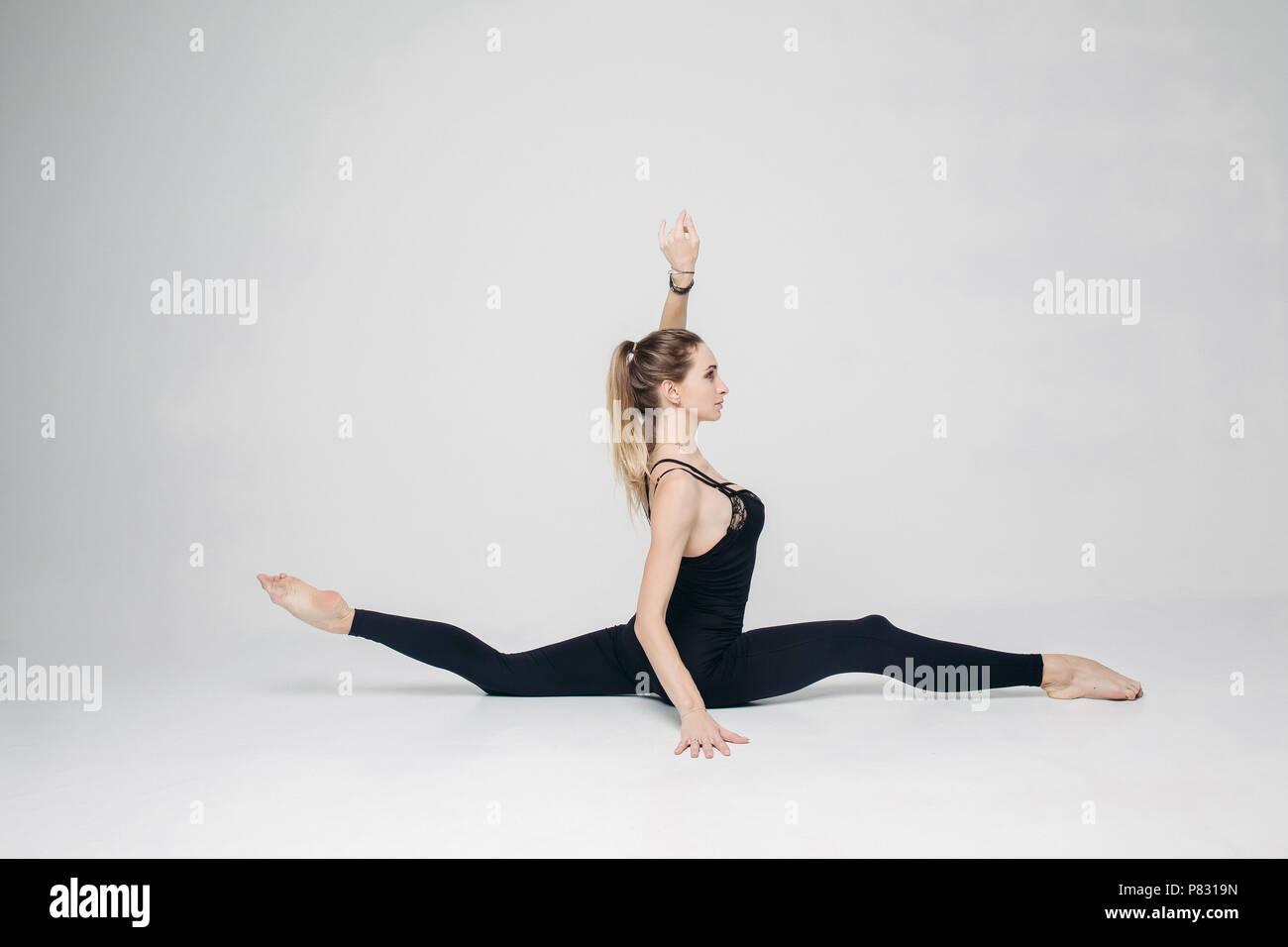 Athletic woman training at studio, sitting in longtudinal twine. - Stock Image