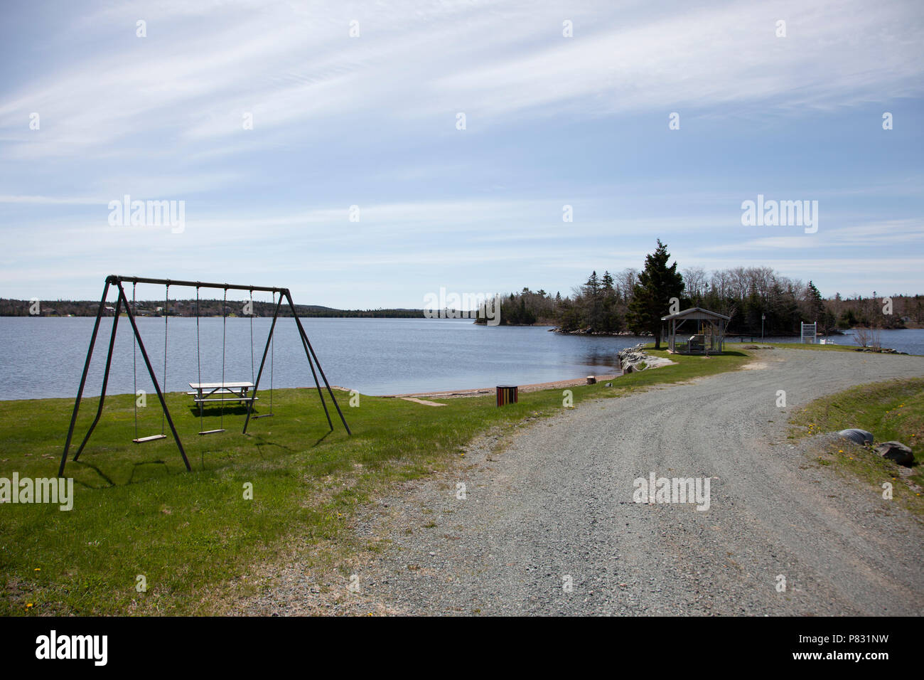A Little Dirt Road Leads Past A Small Beach With Picnic Table And