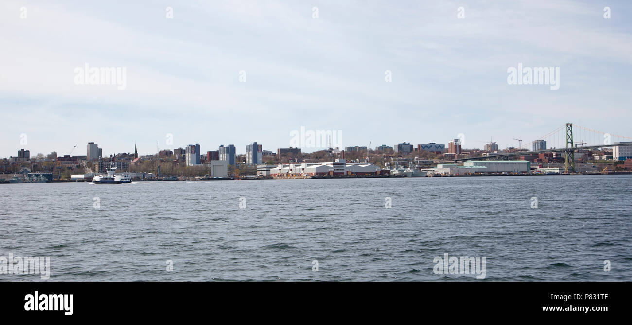 May 12, 2018 - Dartmouth, Nova Scotia: Halifax Harbour from the Dartmouth side, with a ferry crossing, naval shipyard and the MacDonald bridge - Stock Image