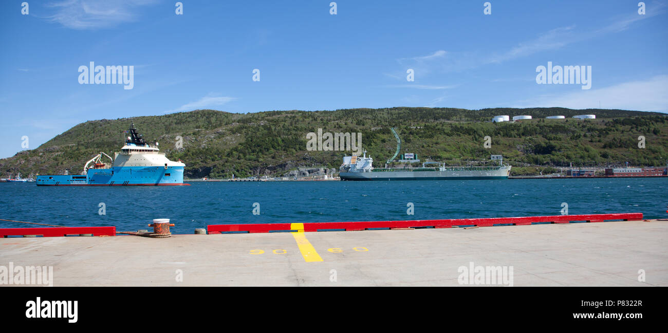 June 23, 2018- St. Johns, Newfoundland: Across the St. Johns, Harbour, the tug supply vessel Maersk Cutter is visible beside an Irving Refinery - Stock Image