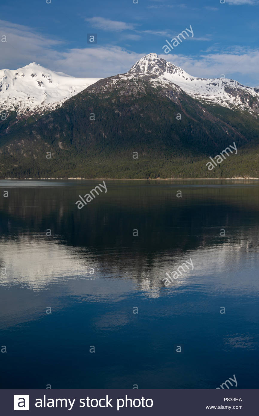 A view of the snow capped Coast Mountains reflected in the ocean waters of Skagway, Alaska - Stock Image