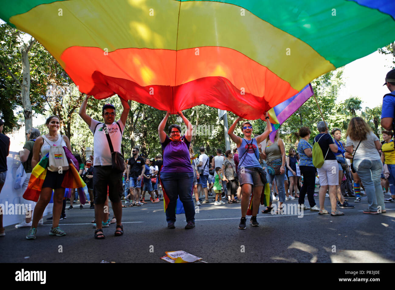 Multicolor flag, symbol of the LGTBI seen being carried by a group of peopla during the 2018 Pride Parade. Thousands of people has been filling the streets and avenues of Madrid on a sunny day for the 2018 gay pride parade after still struggling for gay rights around the world. - Stock Image