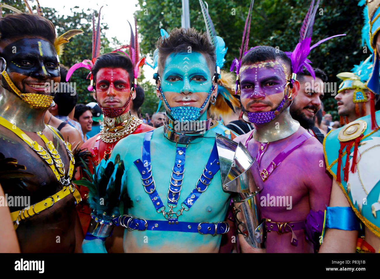 Group of boys with their faces painted with bright colors and dressed in bright colors as well seen during the 2018 Pride Parade. Thousands of people has been filling the streets and avenues of Madrid on a sunny day for the 2018 gay pride parade after still struggling for gay rights around the world. - Stock Image