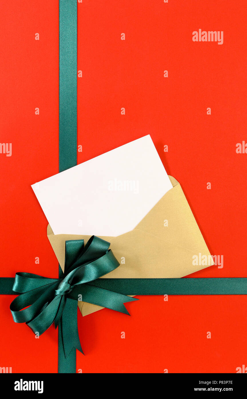 Open Christmas Or Birthday Card With Green Gift Ribbon Bow On Plain Red Background Paper Copy Space Vertical