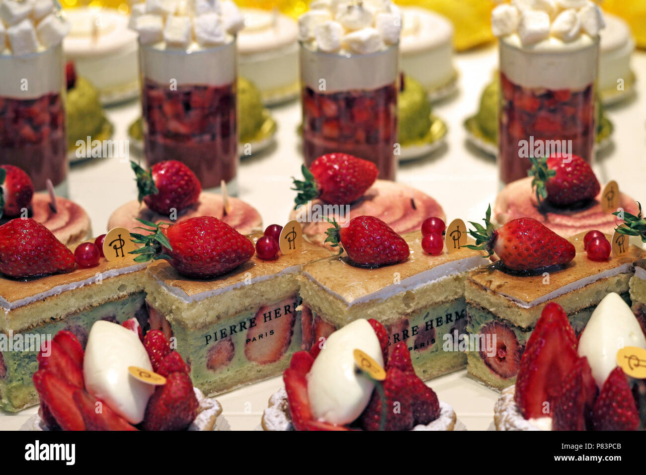 Variety of fresh fruit cakes and desserts displayed in a row, Paris, France, Europe - Stock Image