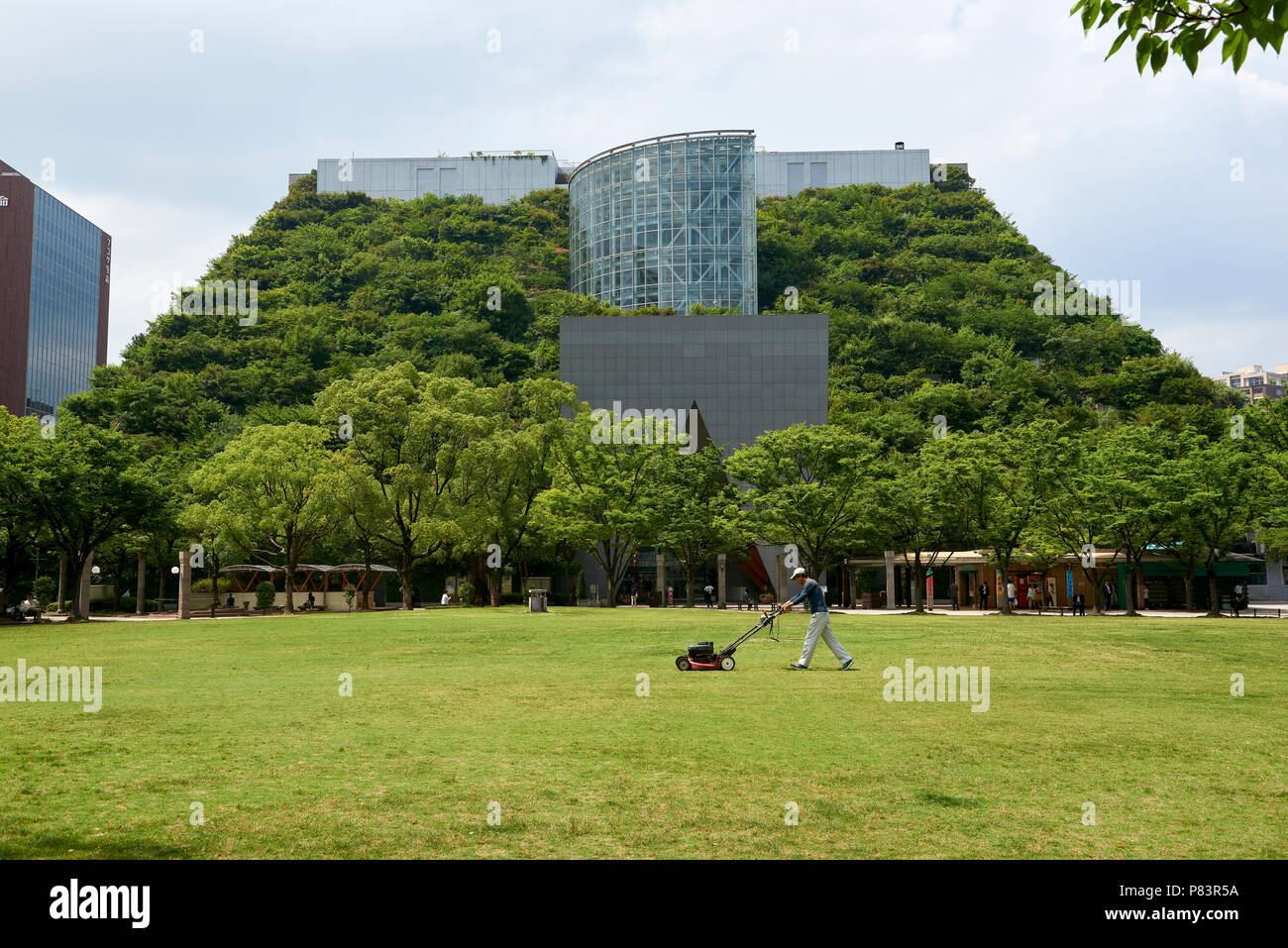 A man mows the lawn in Tenjin Central Park in front of the eco-friendly ACROS building in Fukuoka, Japan. Stock Photo