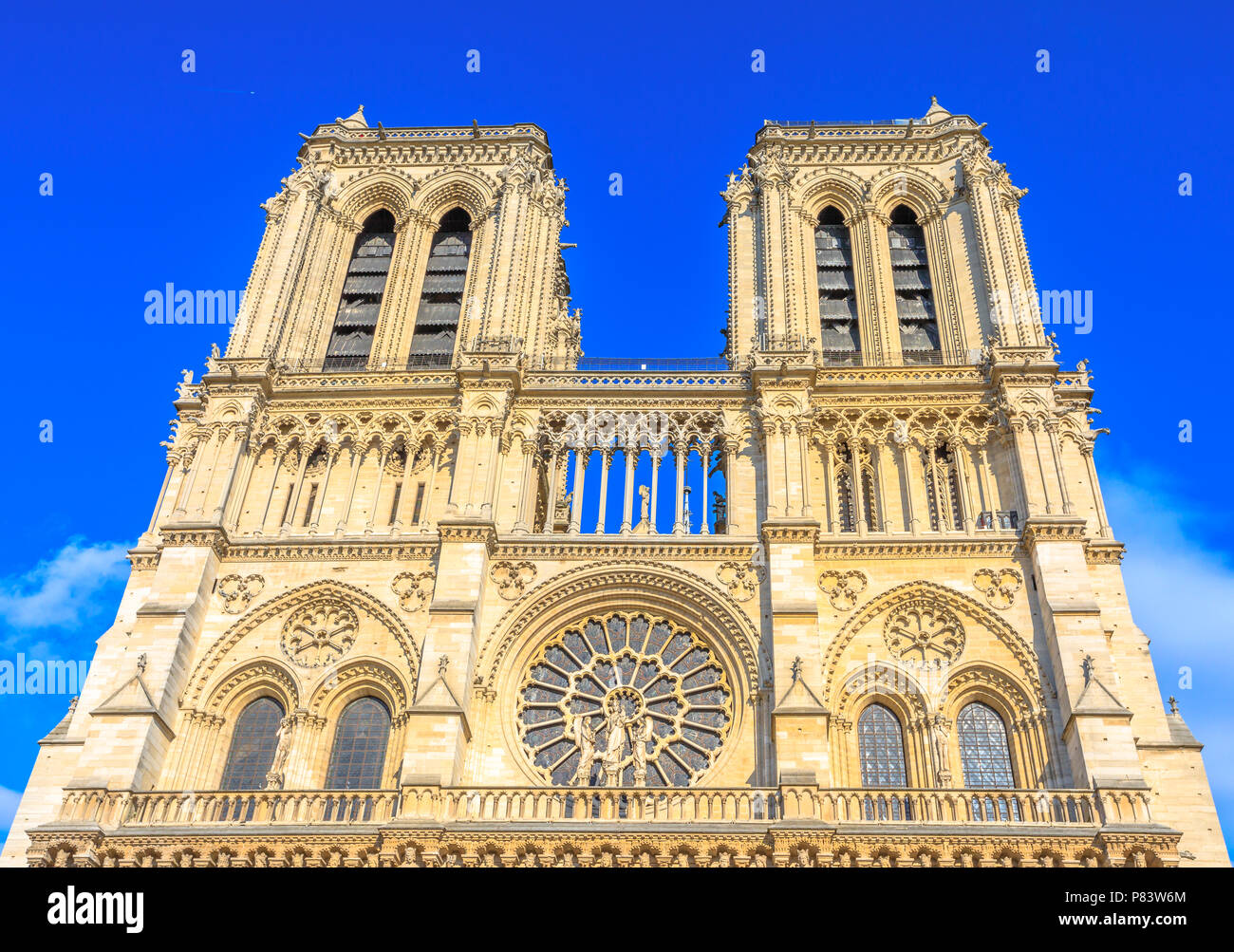 Details of French architecture of Notre Dame cathedral of Paris, France. Beautiful sunny day in the blue sky. Our Lady of Paris church. Central main facade with towers and gothic rosettes. - Stock Image