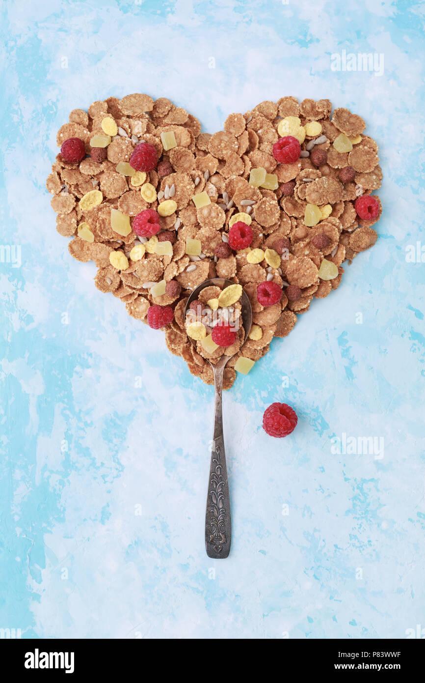 Spoon with heart shape of muesli, corn flakes, raspberries on blue. Healthy eating, breakfast concept. Creative, vertical, minimal. Stock Photo