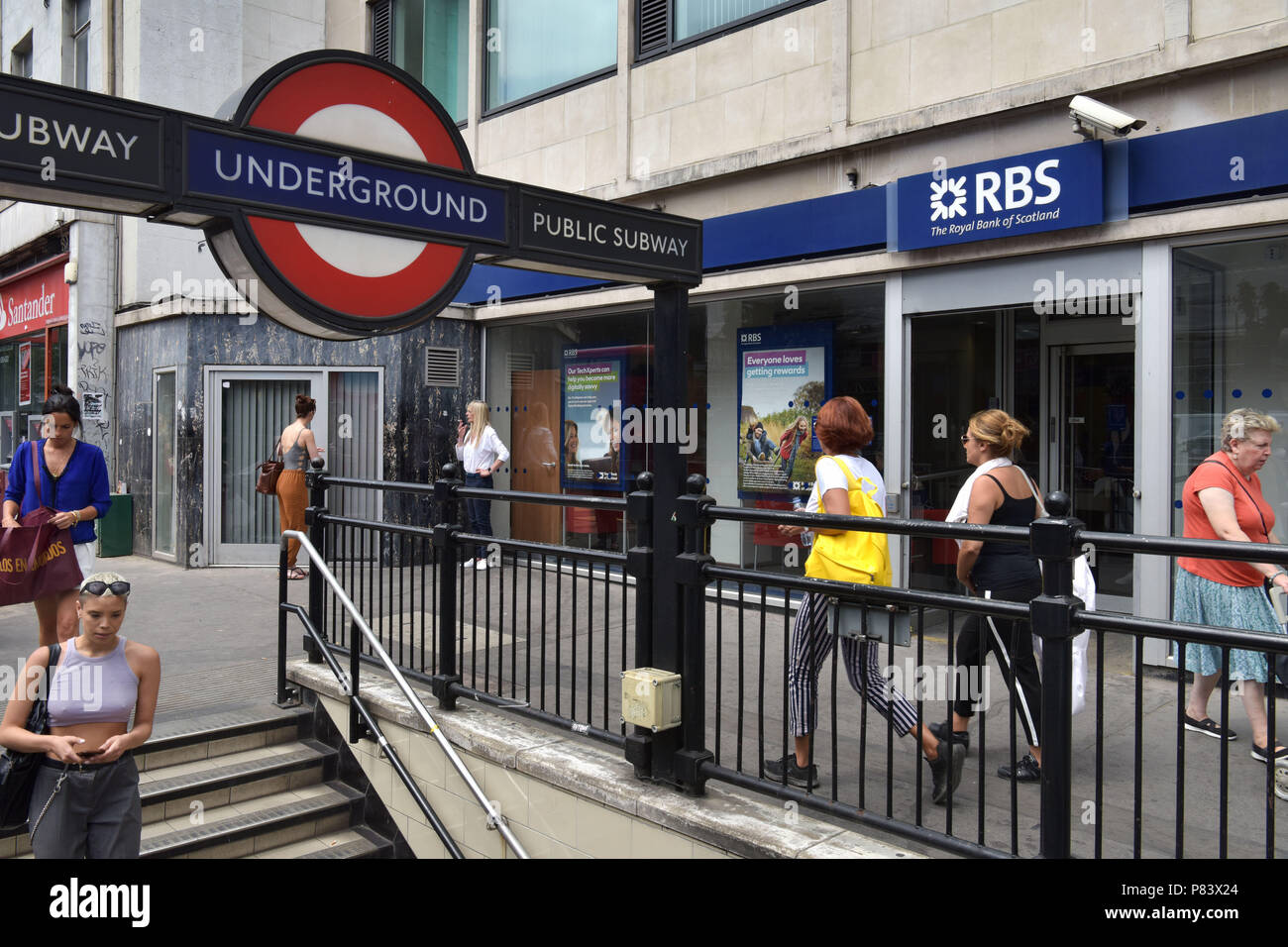 People walk past the branch of the Royal Bank of Scotland bank next to the Notting Hill Gate tube station - Stock Image