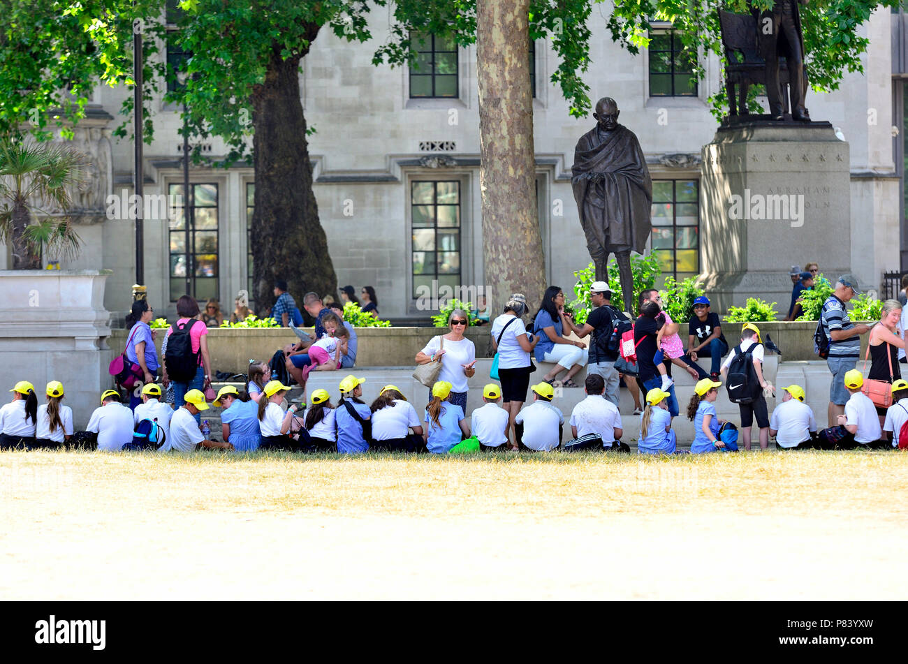 Primary schoolchildren on a school trip in Parliament Square, during a period of hot, dry, weather. London, England, UK. - Stock Image