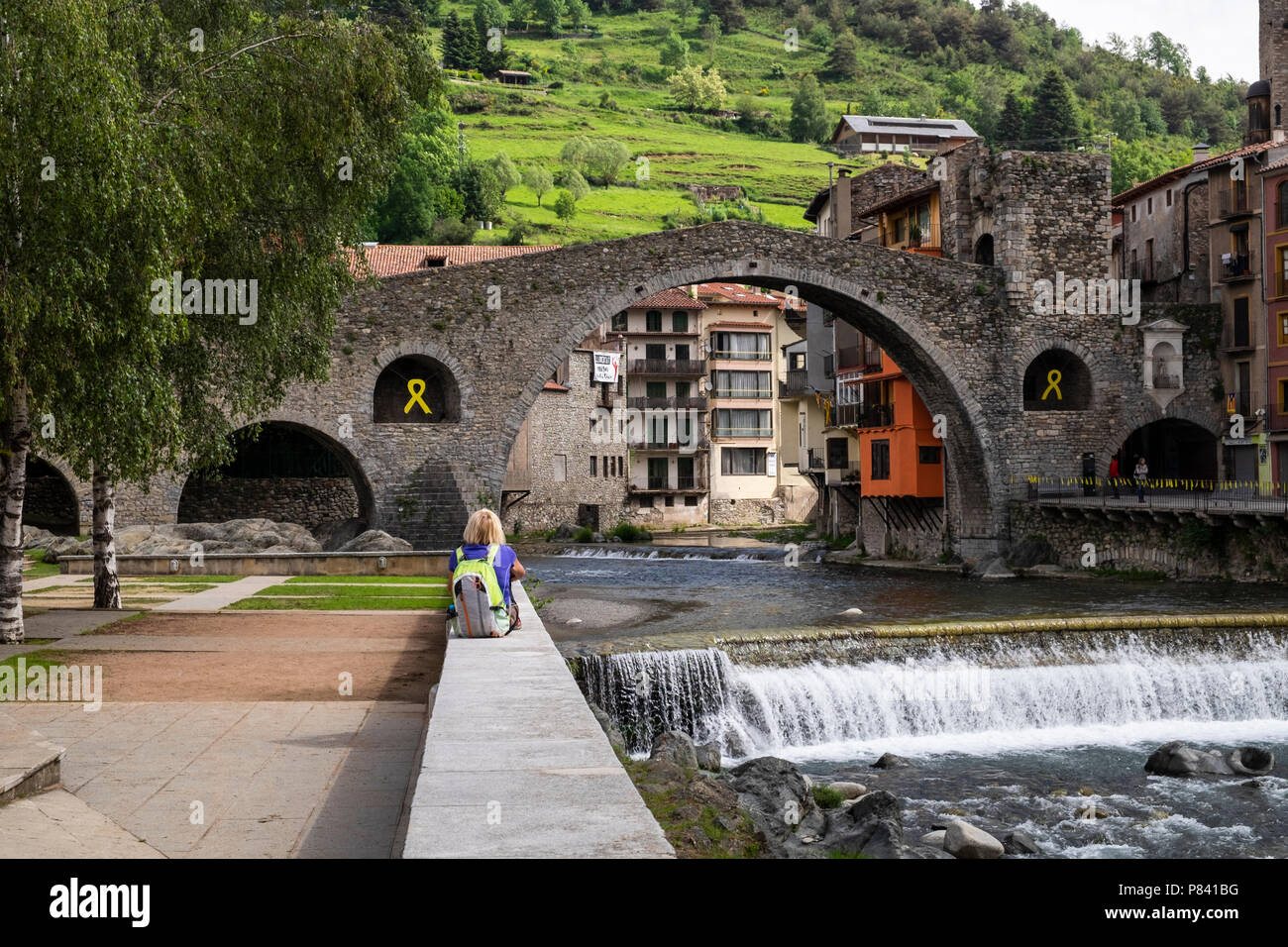 Woman tourist, walker, with backpack sitting by the Pont Neu, the 12th century humpbacked bridge over the River Ter in Camprodon village in the Catalo - Stock Image