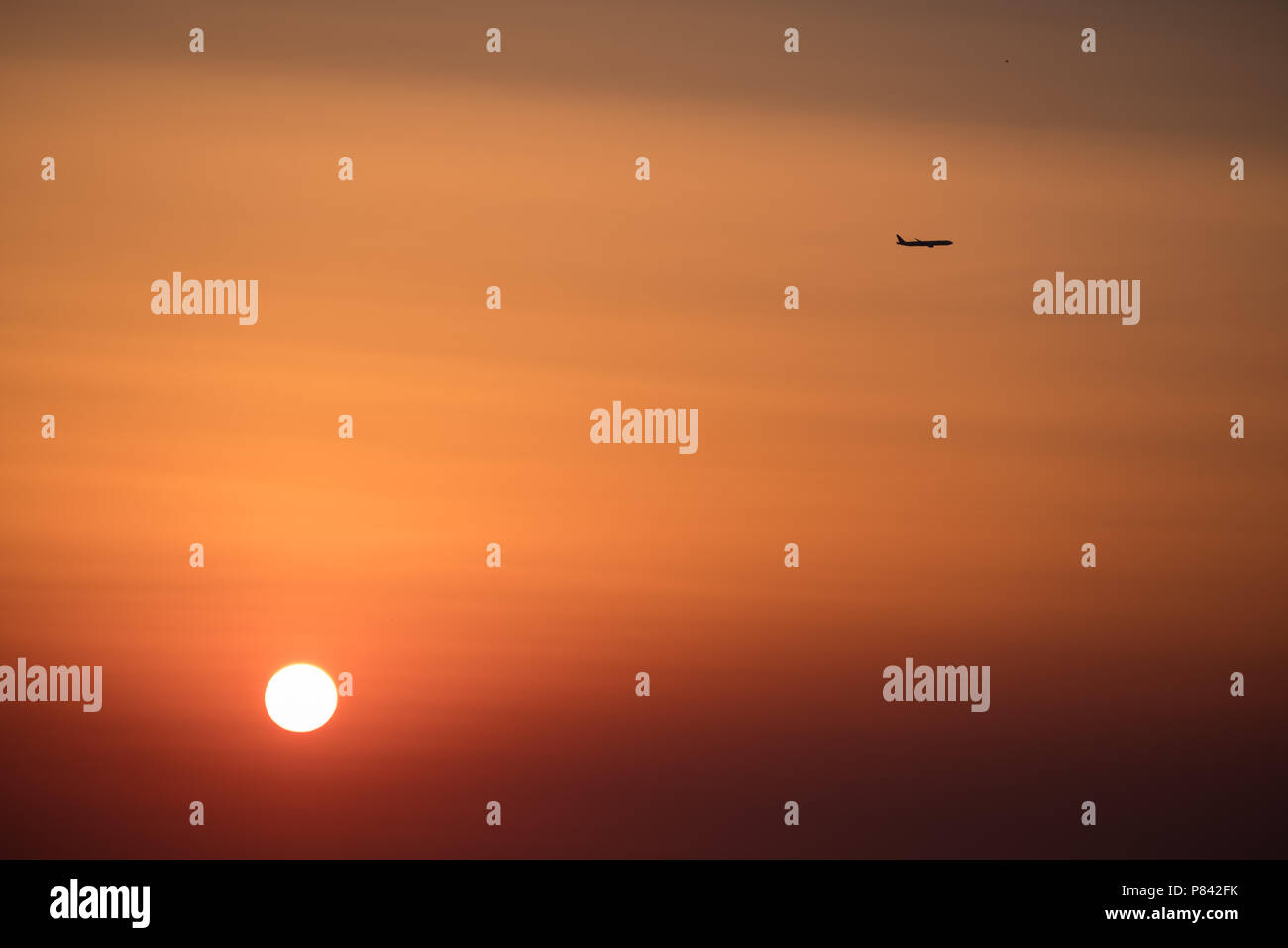 Airplane ( Aeroplane ) passing by a setting sun with gorgeous orange and red sky to its destination, East Attica, Greece, Europe. Stock Photo