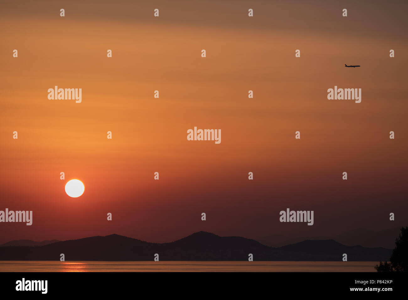 Airplane ( Aeroplane ) passing by a setting sun with gorgeous orange sky and Greek mountain landscape to its destination, East Attica, Greece, Europe. Stock Photo