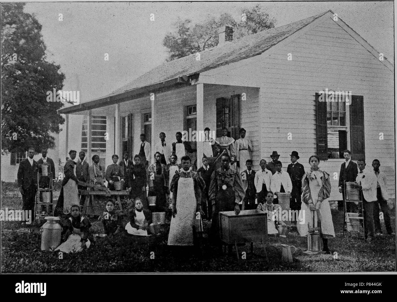 Black and white photograph of Southern University Farm's Dairy Department, comprised by a large group of men and women, some wearing aprons and posing with farm equipment including dairy jugs, with a white, wooden building in the background, located at Southern University in New Orleans, Louisiana, 1893. Courtesy Internet Archive. () - Stock Image