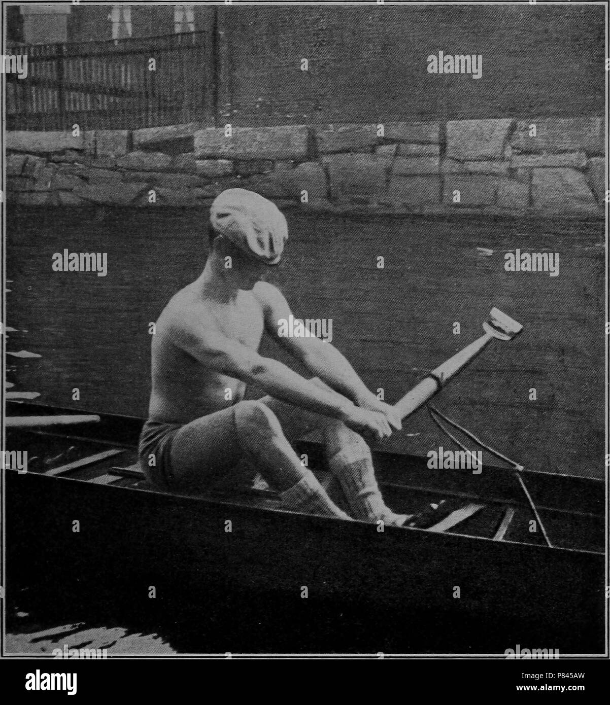 Black and white photograph of a man wearing a cap, shorts, and socks, but no shirt, sitting in a scull and rowing a single oar with both hands, with a stone embankment in the background, 1906. Courtesy Internet Archive. () - Stock Image