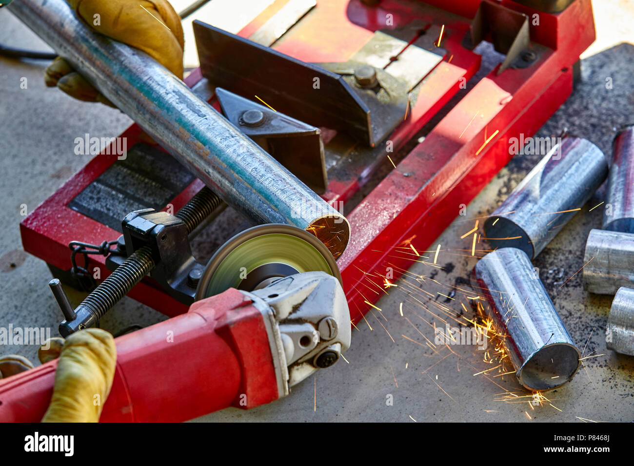 A construction worker using a grinder on a newly cut galvanized steel pipe - Stock Image