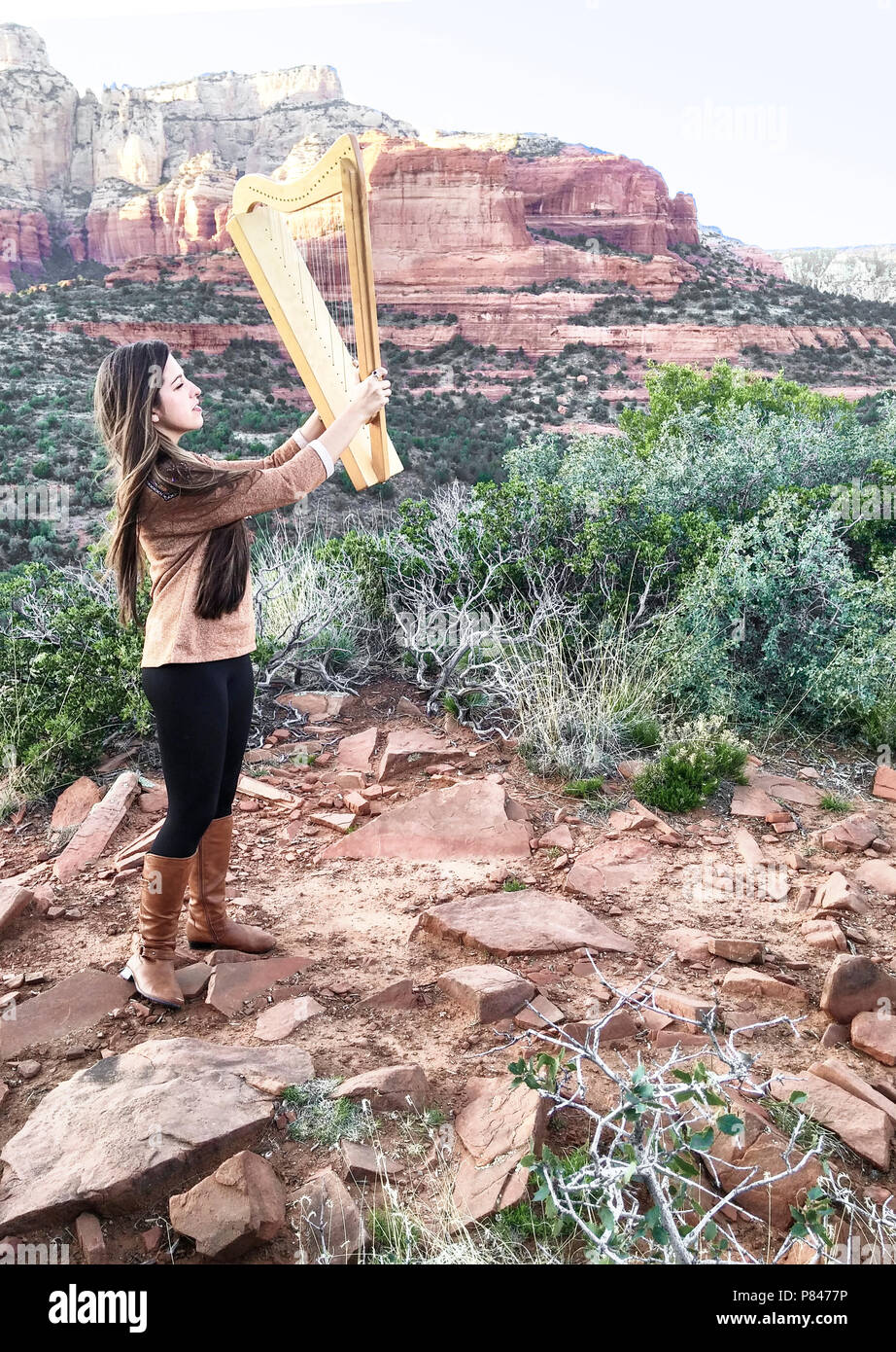 Aeolian Wind Harp raised to the breeze in mystical, red rock desert in Sedona, Arizona. A beautiful young model-released woman plays the instrument - Stock Image