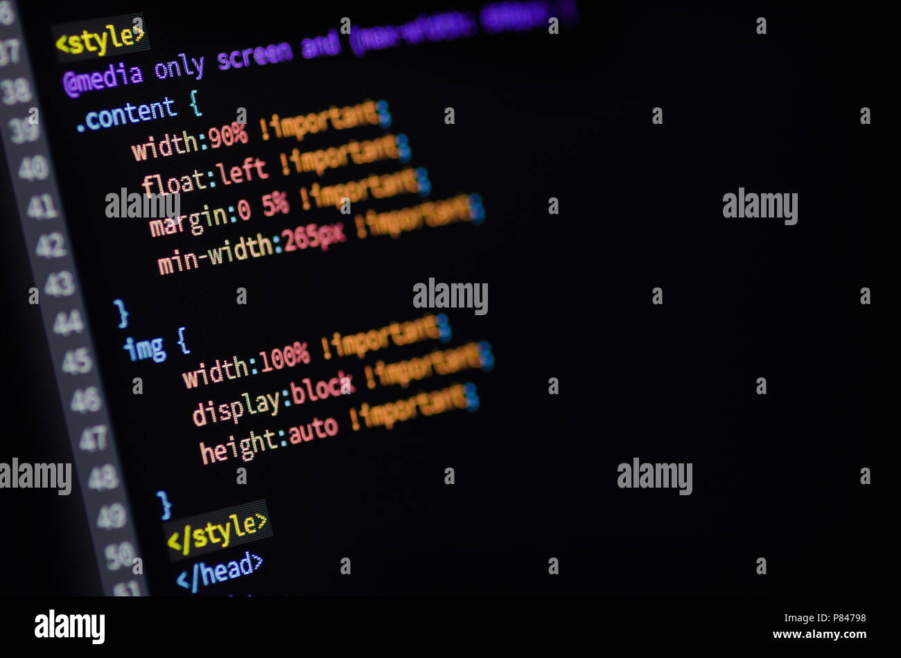 Close-up of media query, html and css code of web page displayed on a computer monitor - Stock Image