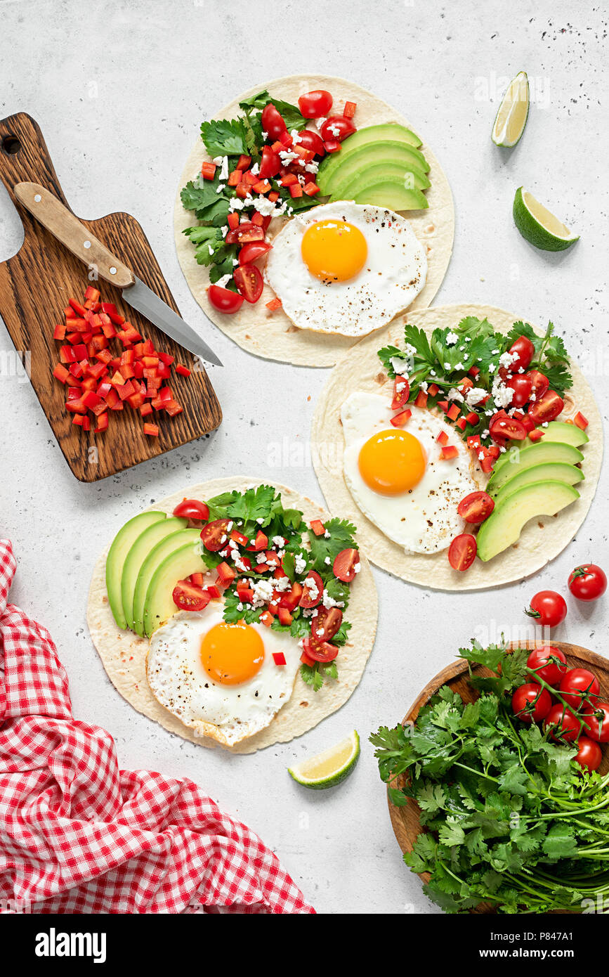 Tortilla with avocado, salsa and egg on concrete background. Top view Stock Photo