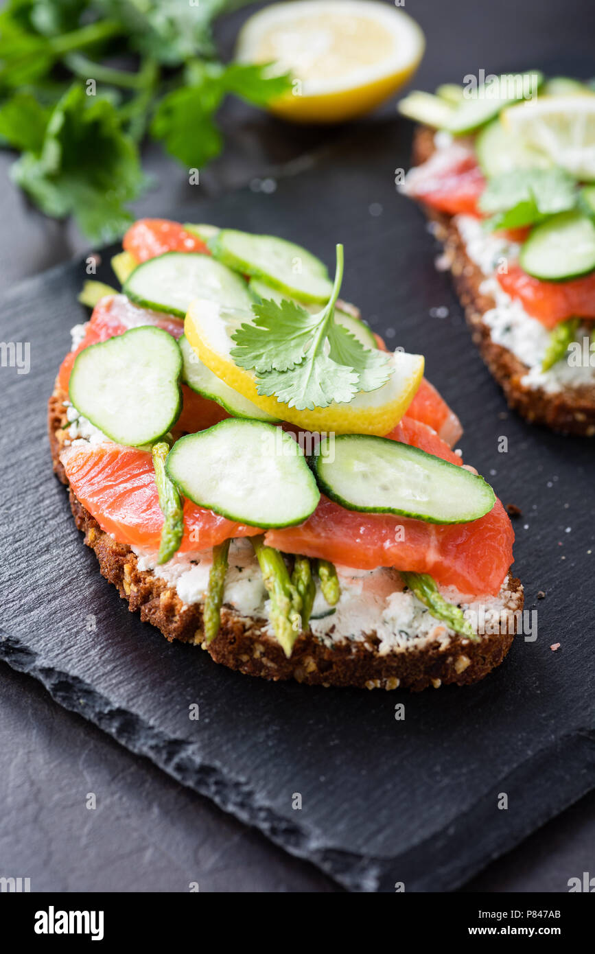 Sandwich with salmon, cream cheese and cucumber on slate background, closeup view, selective focus - Stock Image