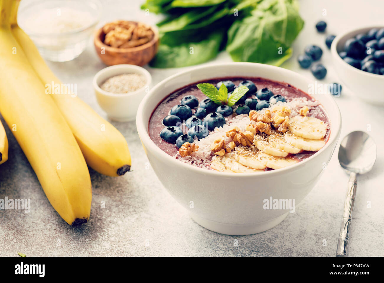 Acai smoothie bowl on grey concrete background. Smoothie with superfood toppings banana, walnut, coconut, chia seeds and fresh blueberries. Selective  - Stock Image