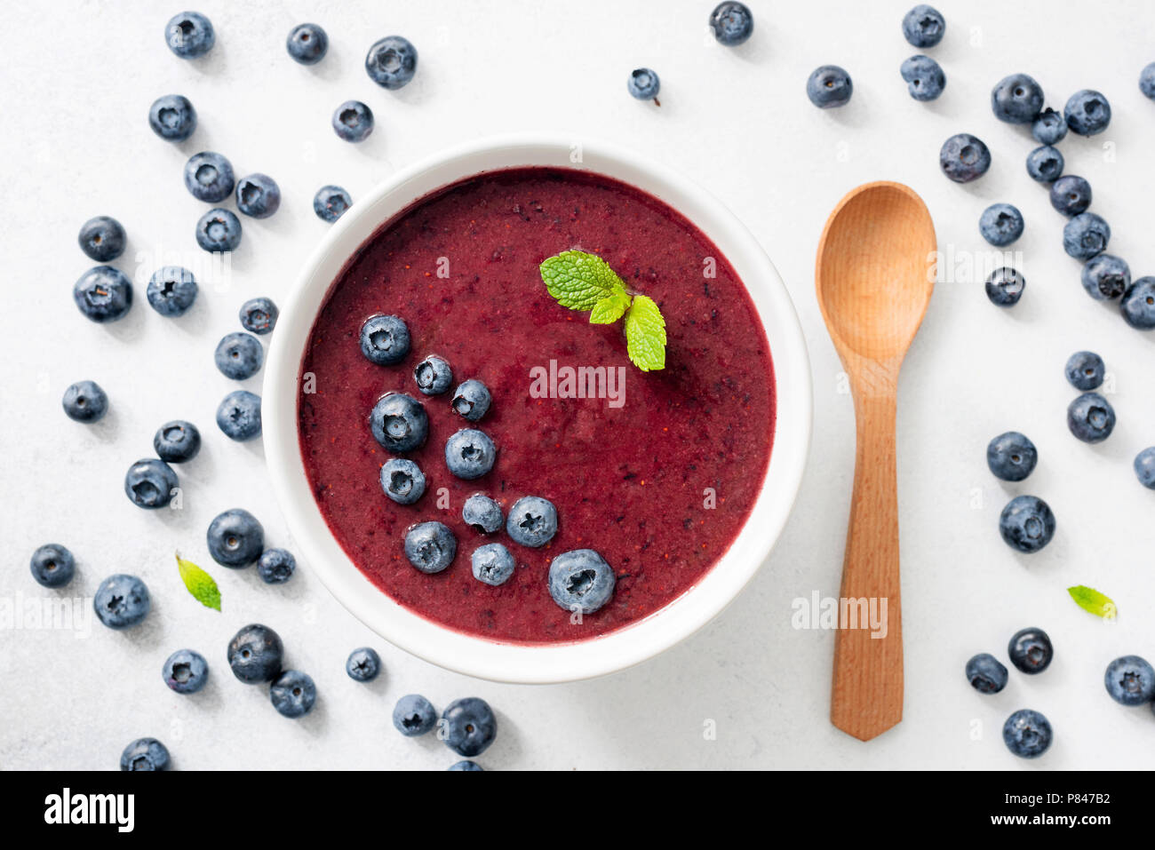Acai blueberry smoothie bowl on white background top view. Trendy superfood, cleansing, detox and nutrition meal - Stock Image
