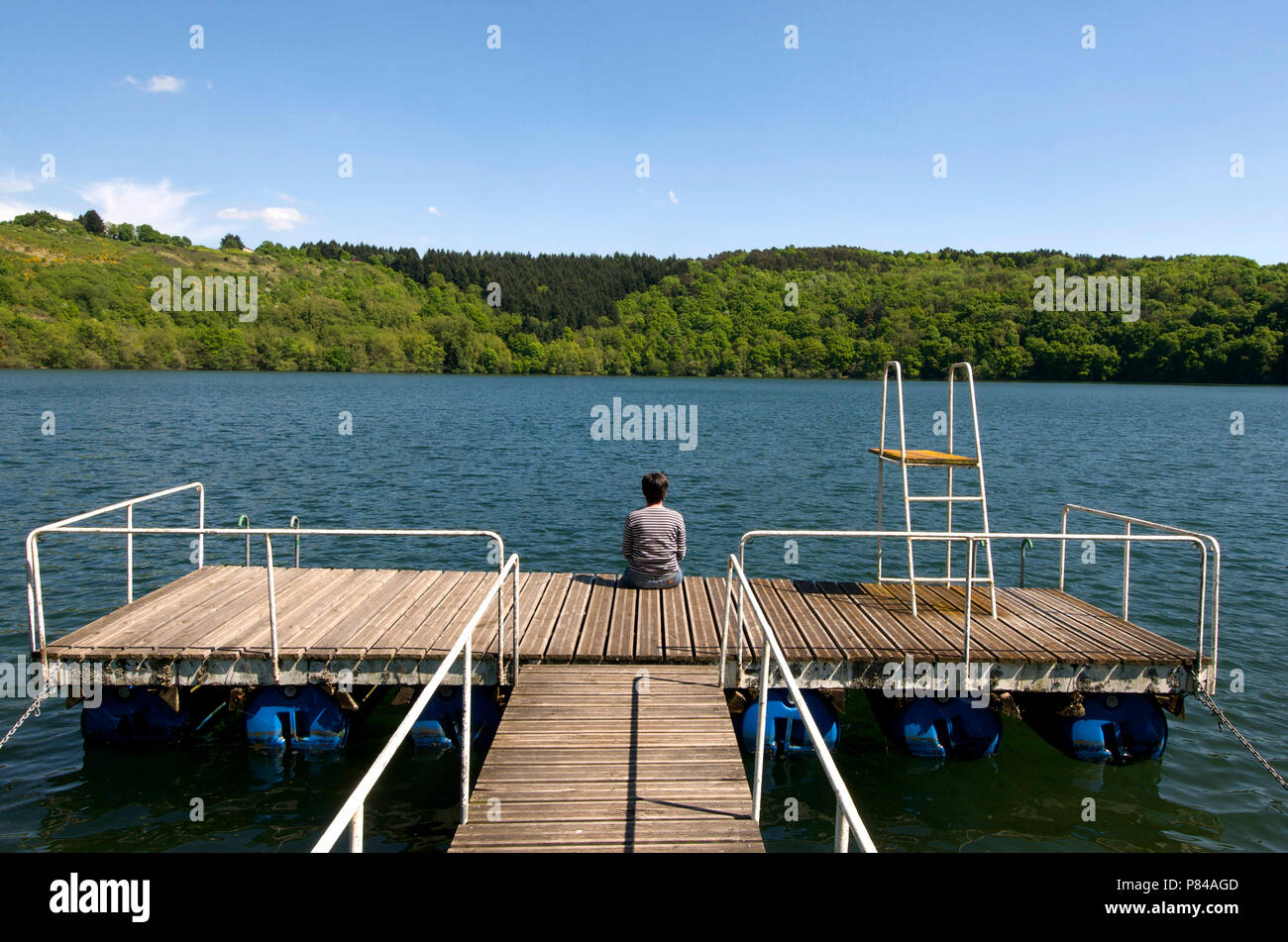 Woman sitting on a pontoon looking out over a lake, Auvergne, France - Stock Image