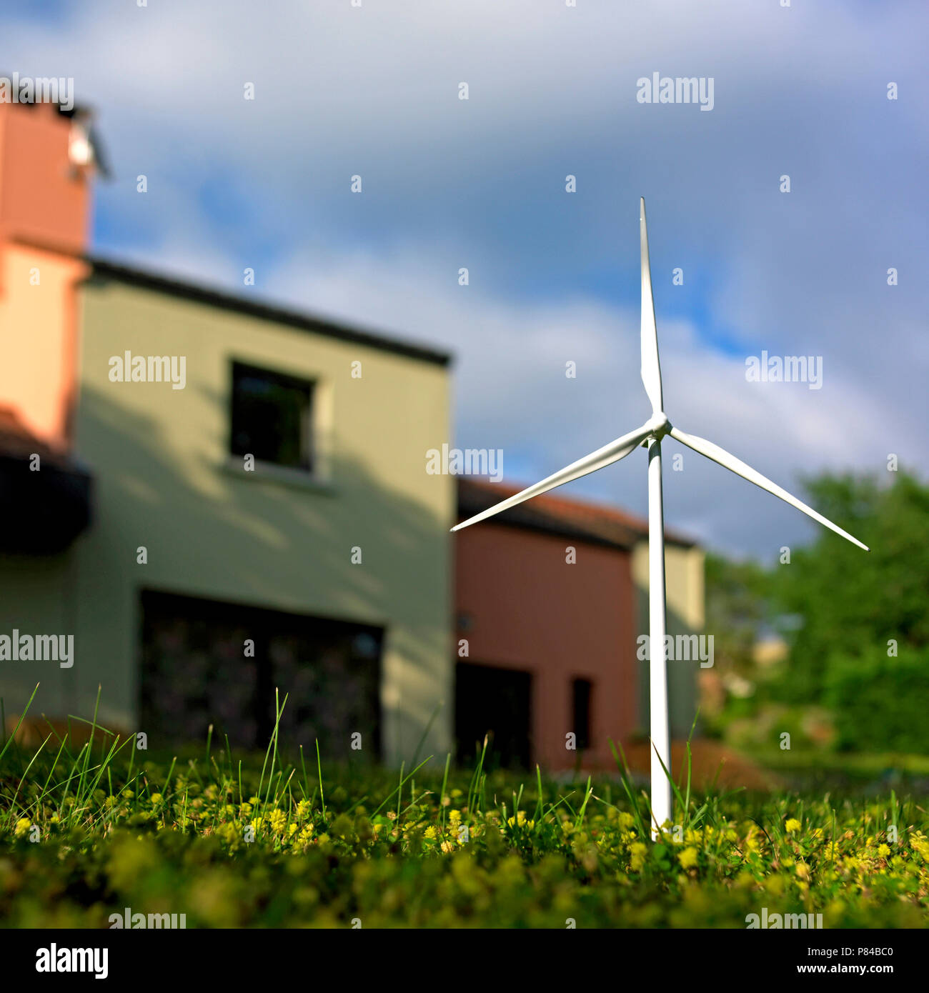 Miniature wind turbine in the grass in front of a sunny house Stock Photo