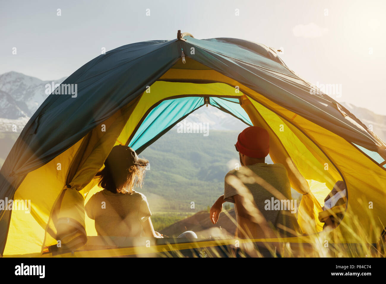 Couple rest in tent against mountains sunset - Stock Image