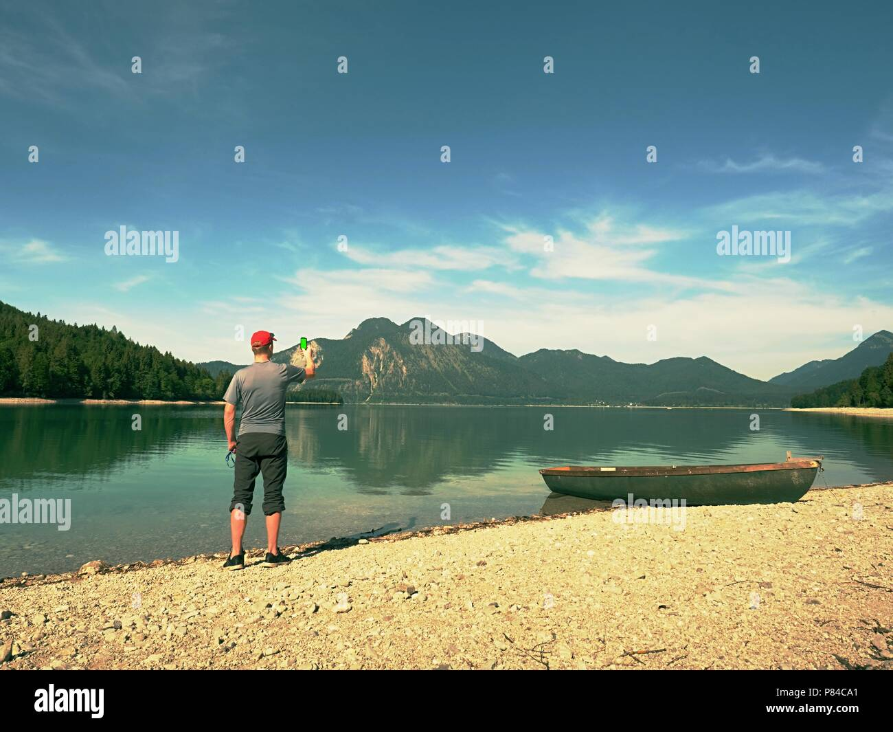 Photo traveler is taking memory photo of lake scenery. Blue lake between high mountains, peaks touch in blue sky. Travel lifestyle concept - Stock Image
