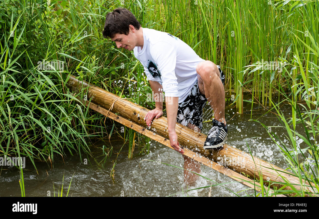 Biddinghuizen, The Netherlands - June 23, 2018: Man during a mud run (mudraise, charity) in the mud and in the water climbing a tree trunk. - Stock Image