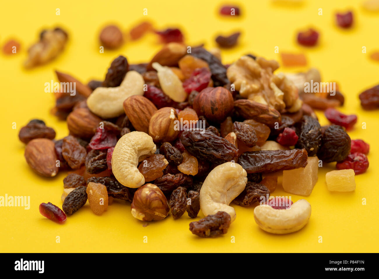 Close up of mix of dried fruits and nuts on a yellow background - Stock Image