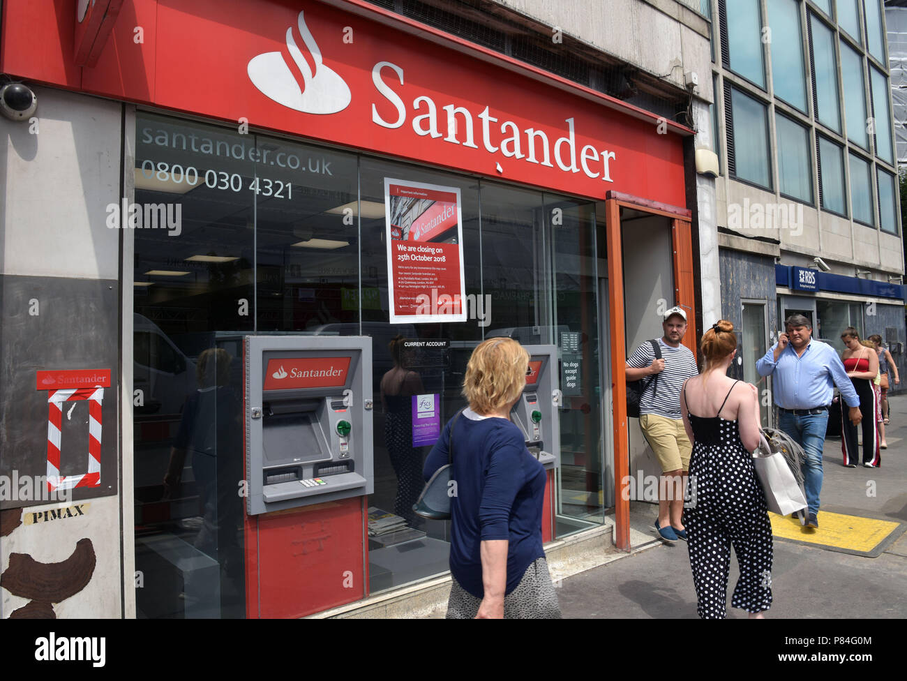 People walk past the Santander bank in Notting Hill, London, next to RBS. As part of a programme of closures this branch will close in October 2018. - Stock Image