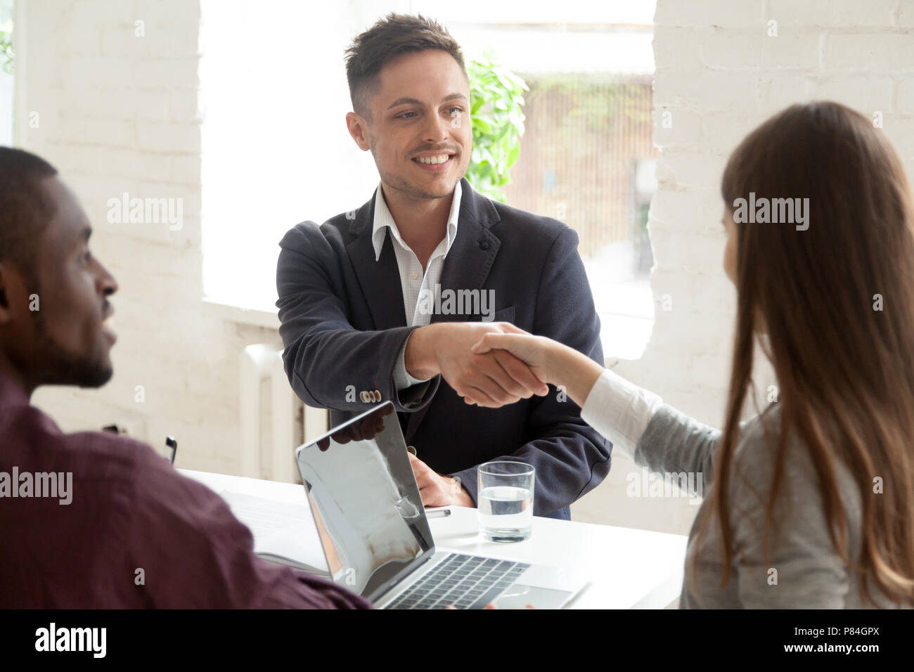 Smiling male worker shaking hand of young female colleague at business meeting, multiracial coworkers cooperating, partners handshaking greeting or ma - Stock Image