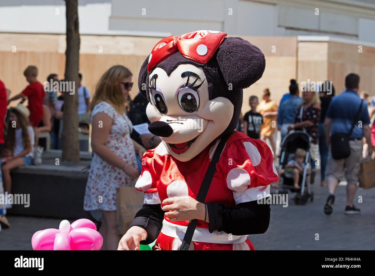 Street Entertainer Dressed As A Minnie Mouse Selling Funny Shaped Balloons To The Public In Liverpool Uk