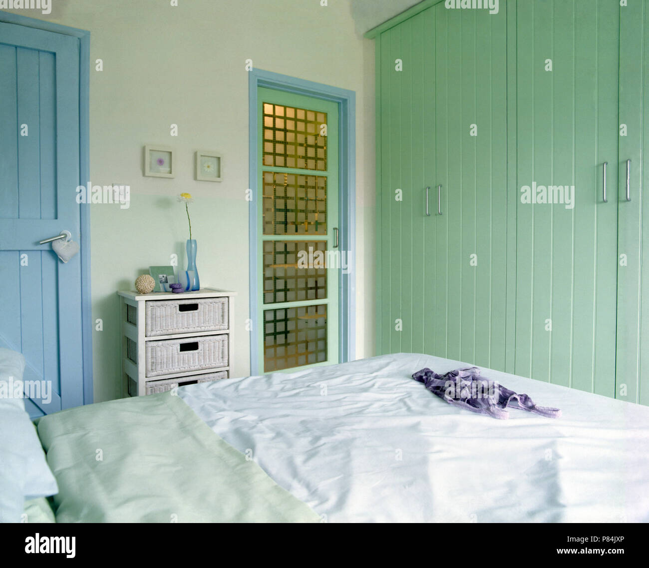 Pale Green Tongue+groove Fitted Wardrobe In A Country Bedroom With A Glass  Door To The En Suite Shower