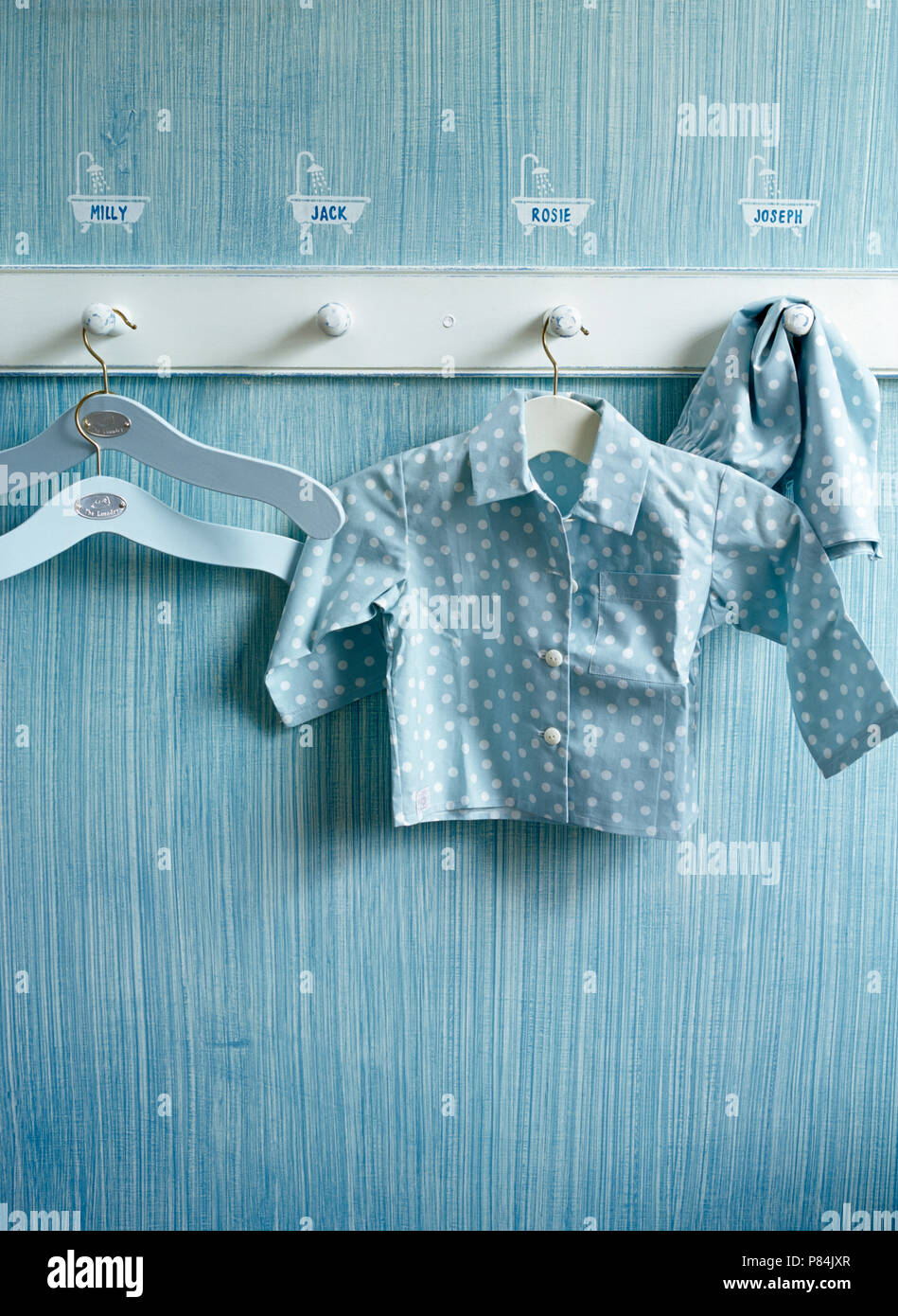 Close-up of a pegboard with a pair of children's pyjamas on a wall with a combing paint effect and stenciled children's names - Stock Image