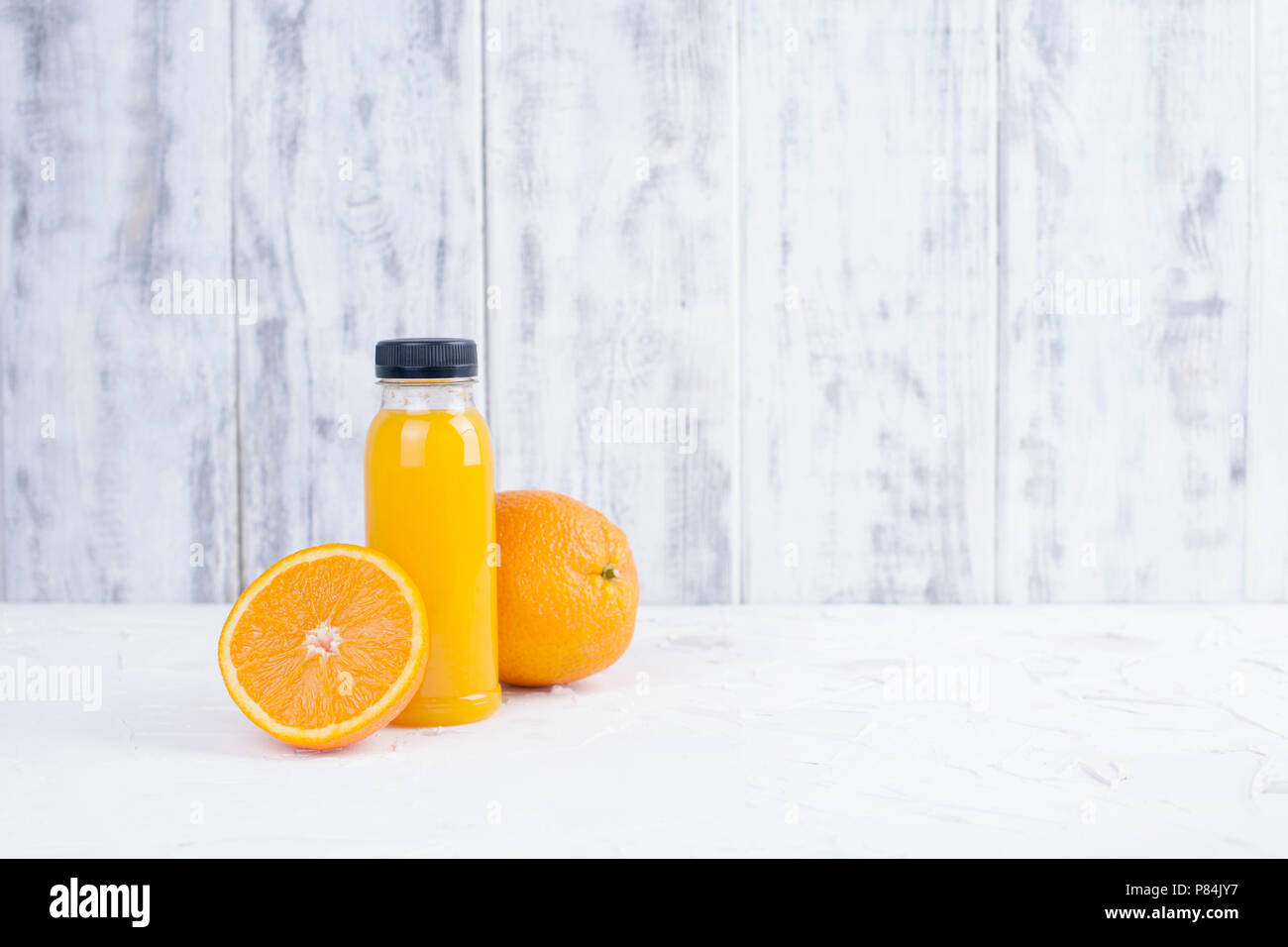 Bright oranges and orange juice in a plastic bottle. White wooden background. Copy space - Stock Image