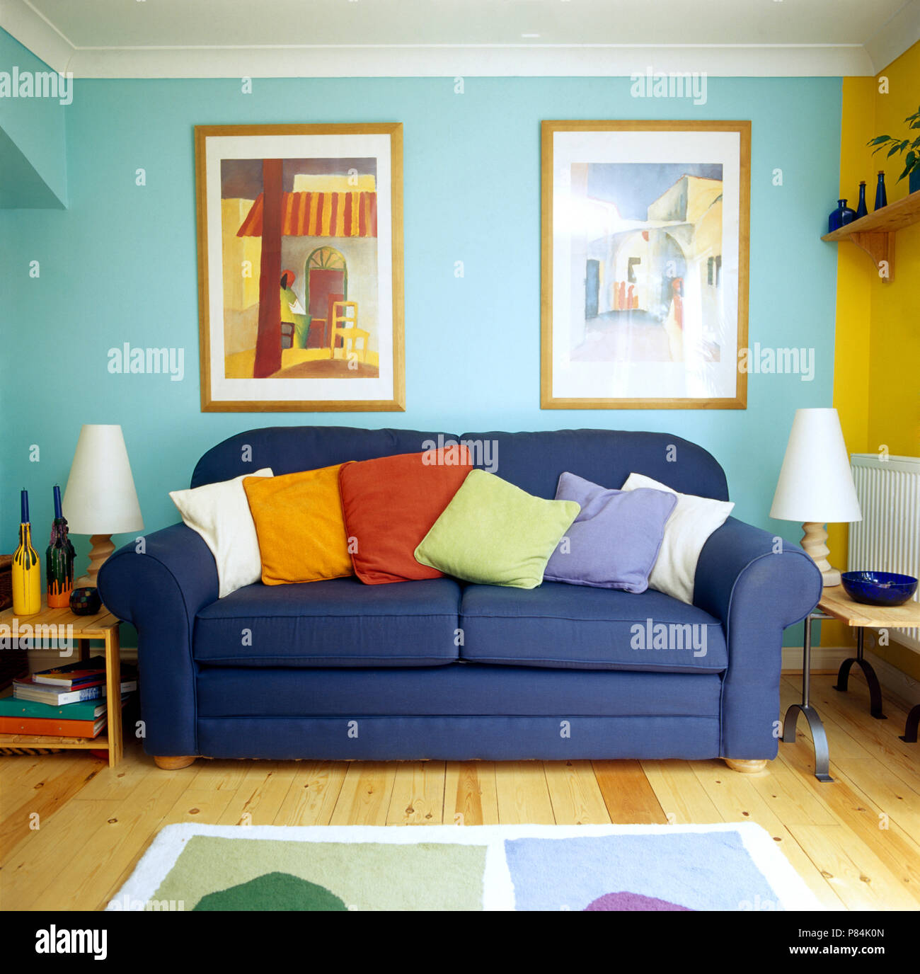 Colourful Pictures On Wall Above A Blue Sofa With Multi Coloured Cushions  In A Pale Turquoise Economy Style Living Room