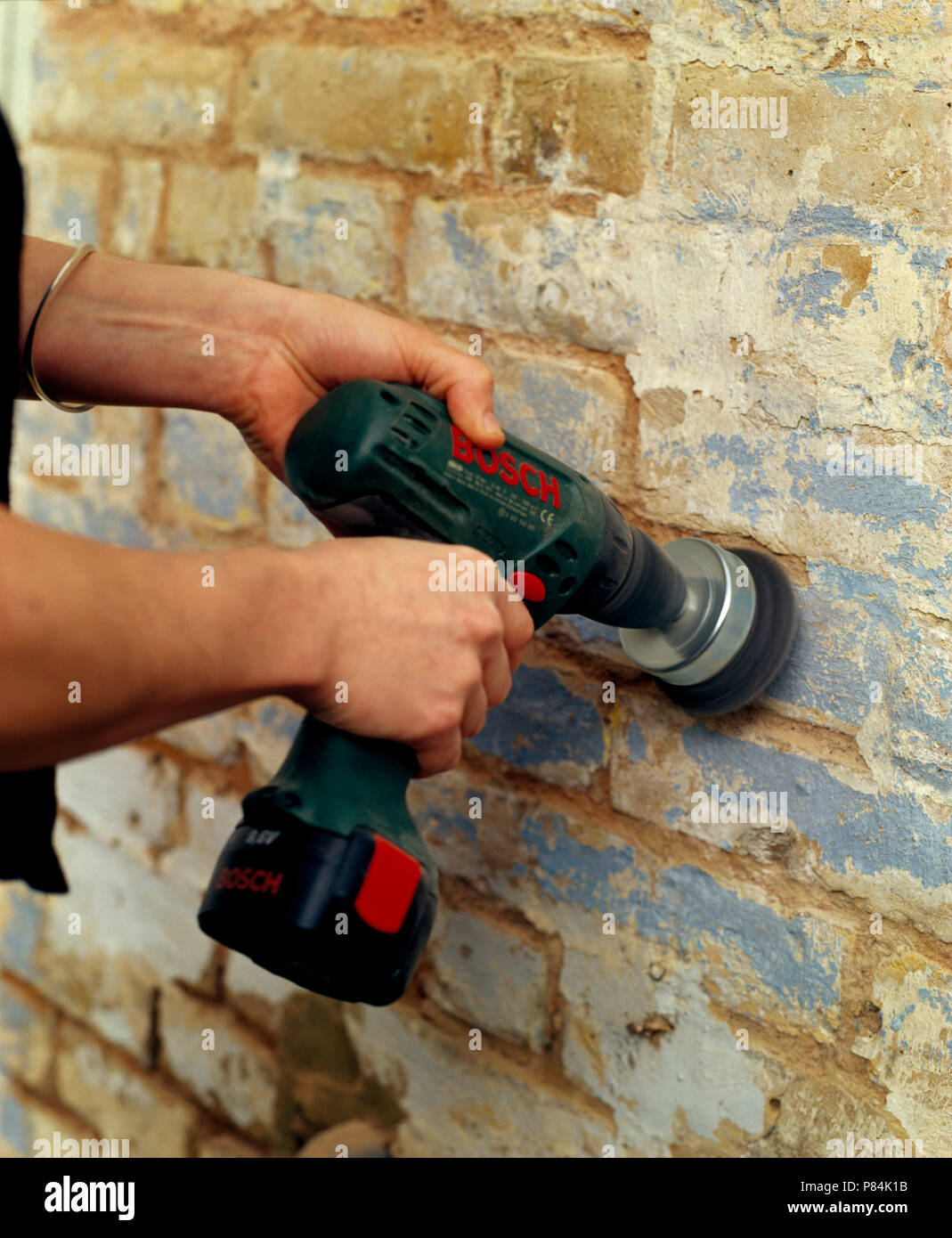 Close-up of hands using the brush attachment on an electric drill to clean an outside wall - Stock Image