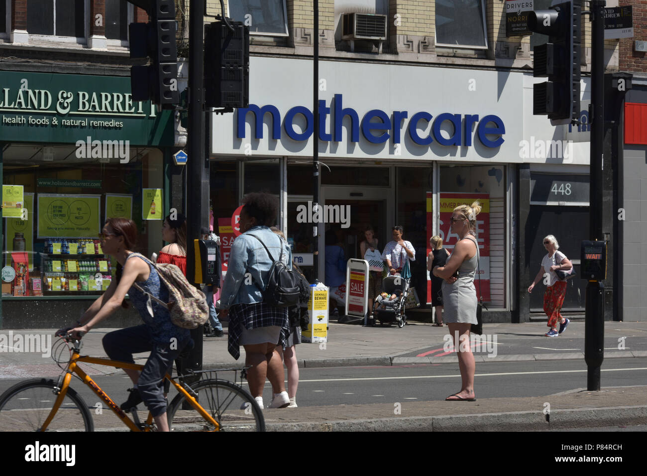 People walk past a branch of the specialist retailer Mothercare on the Holloway Road in North London - Stock Image