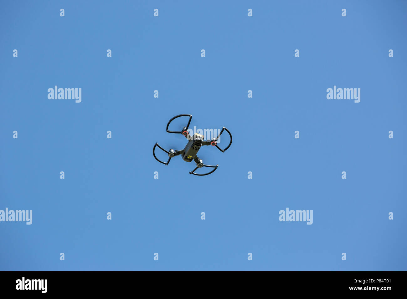 A camera carrying drone flying in a clear blue sky - Stock Image