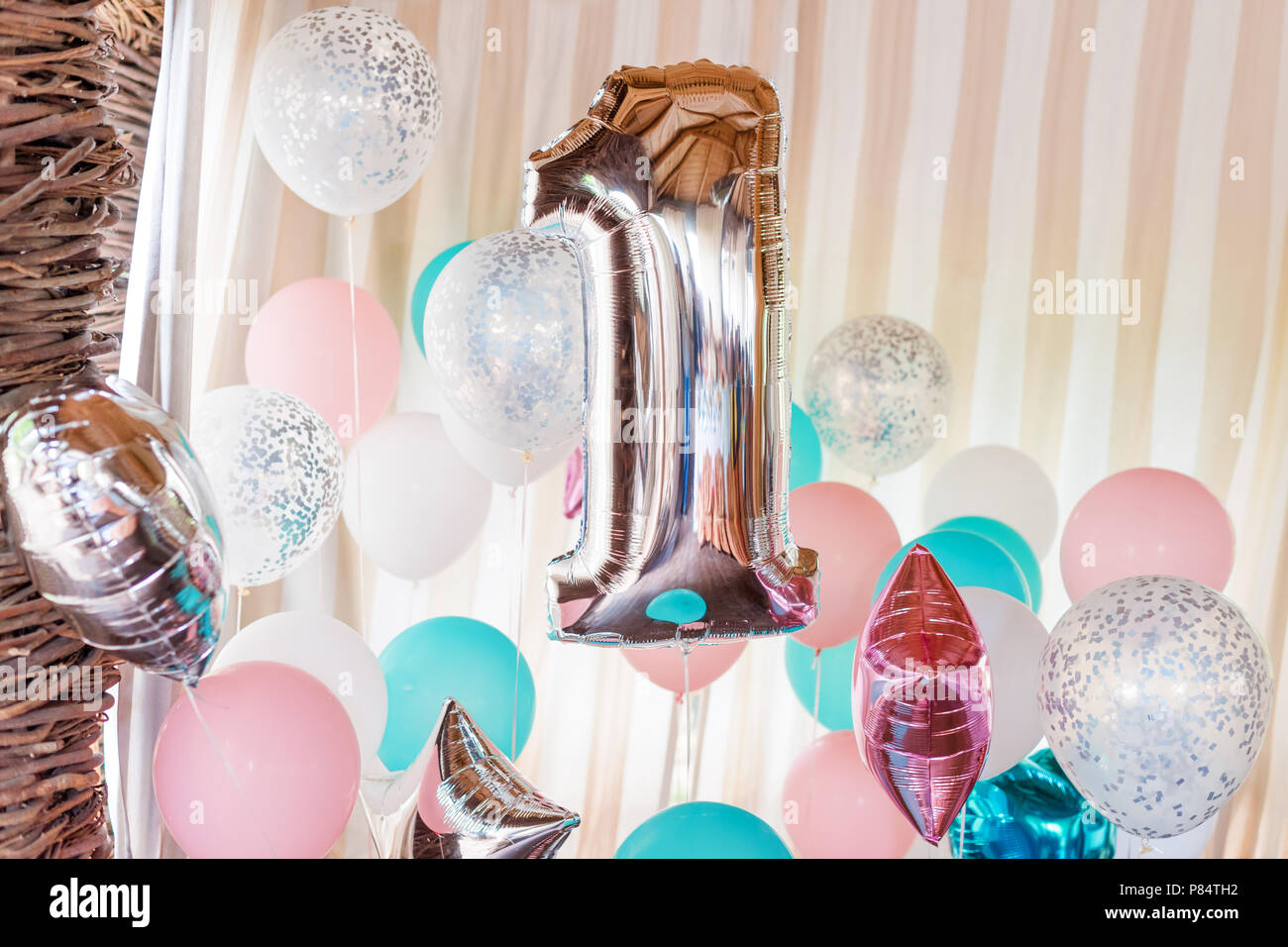 Pink, silver and blue inflatable balloons on ribbons - number 1. Decorations for birthday party. Metallic design balloon Stock Photo
