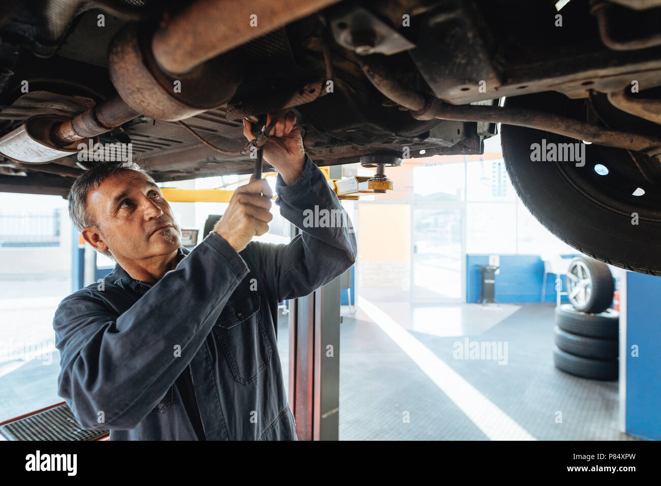 Car mechanic working under a automobile in garage. Auto mechanic repairing a vehicle in service station. - Stock Image