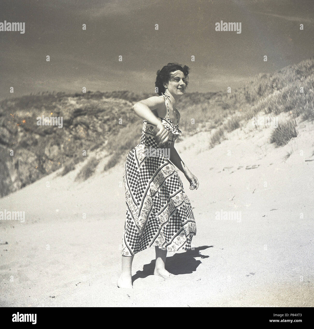 1950s, summertime and a young lady in a long patterned dress playing frisbee on a sandy beach, England, UK. Stock Photo