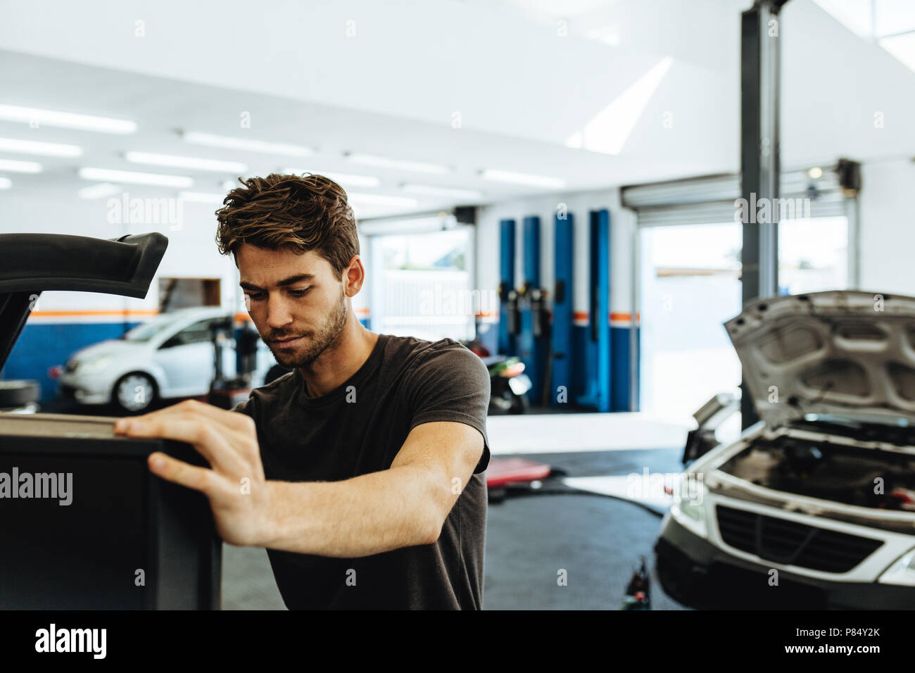 Young mechanic doing car check up on computer. Mechanic using computerized equipment to diagnose a car in service station. - Stock Image