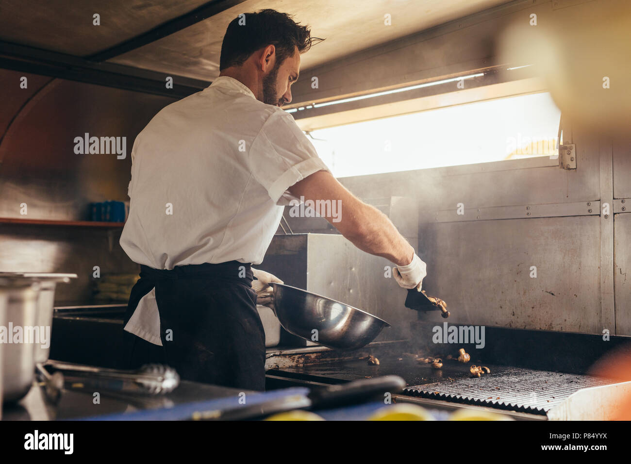 Male cook making some food in a food truck parked under a tree. Man chopping vegetable on his food truck. - Stock Image