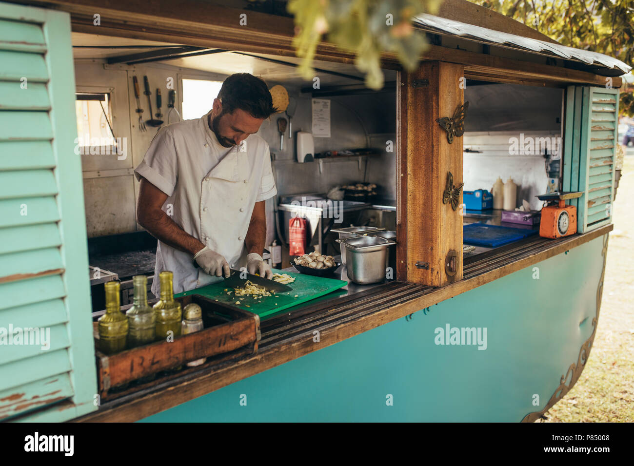 Man cooking some food in a mobile food truck parked under a tree. Man chopping vegetable on his food truck. - Stock Image