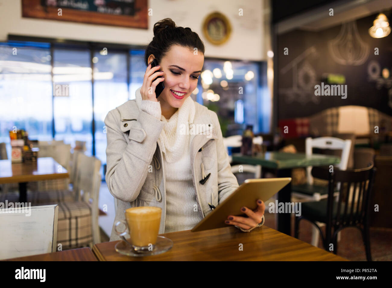 Attractive young woman using tablet in cafe Stock Photo